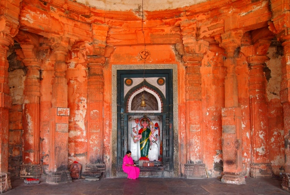 a lady worships in one of the shrines