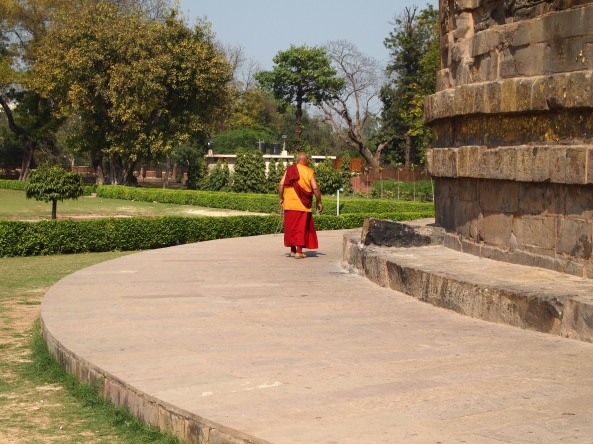 a monk walks around the stupa at Sarnath
