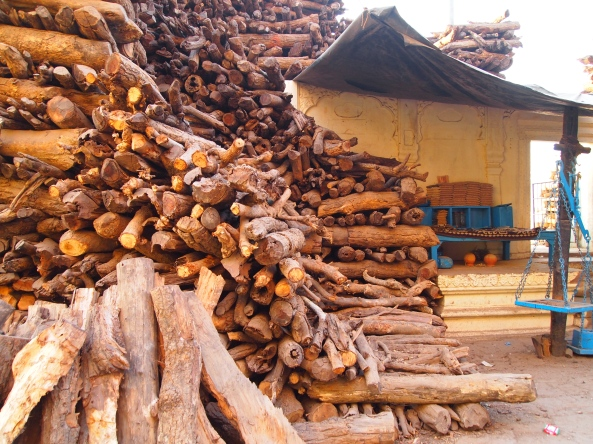 huge stacks of wood at the burning ghat