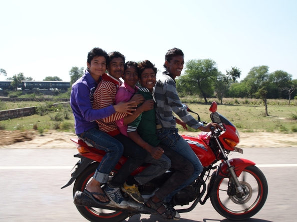 while driving out of Agra, these boys rode along beside us and tossed roses into our car