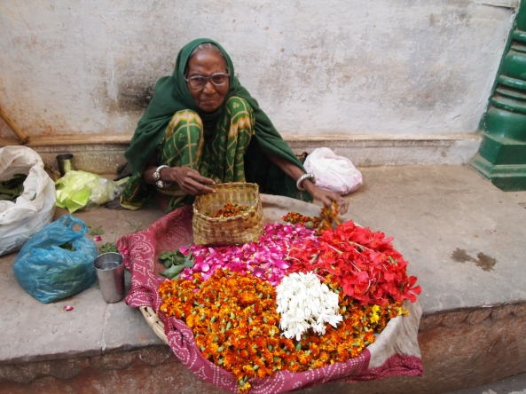 an Indian woman selling flower blossoms
