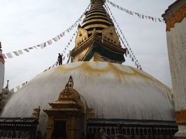 a monk splashes arcs of saffron paint over the stupa in a lotus-flower pattern