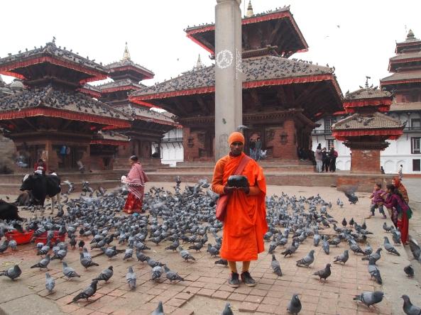 a monk stands silently seeking alms in front of Jagannath Mandir