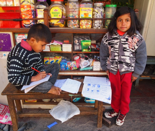 this little boy and girl are working diligently in their schoolbooks