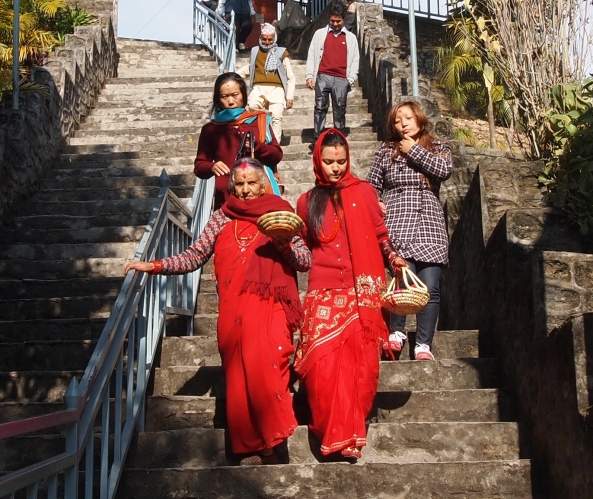 two HIndu ladies walking down from the temple wearing auspicious red
