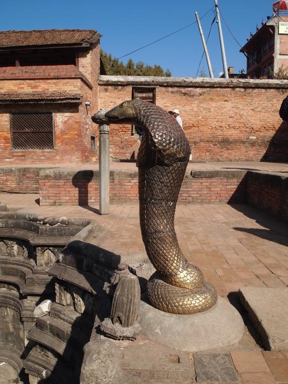a nag figure looking over the bathing tank at Naga Pokhari