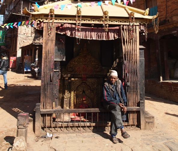 a Nepali man relaxing at a little shrine
