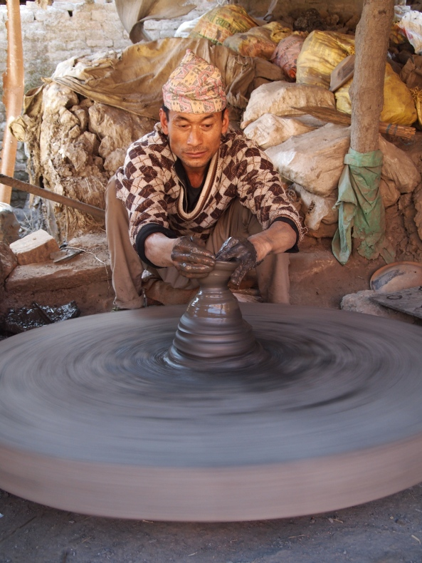 a potter using the traditional hand-powered wheel