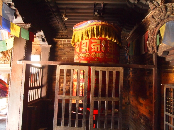 a large red prayer wheel in a corner